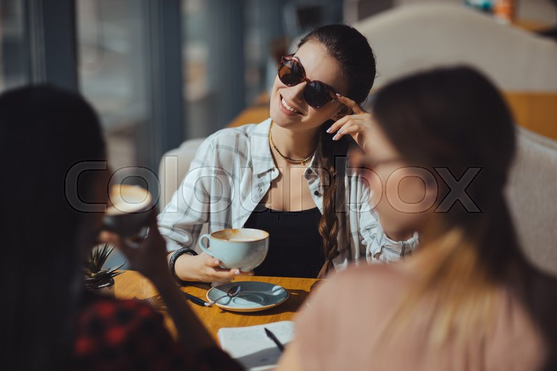 Young attractive multicultural women on coffee break in cafe , stock photo
