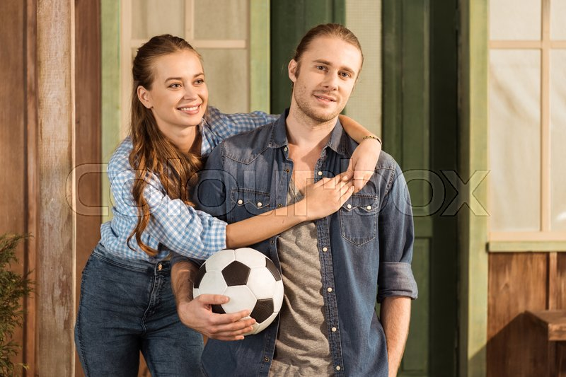 Young caucasian couple holding soccer ball and hugging, stock photo