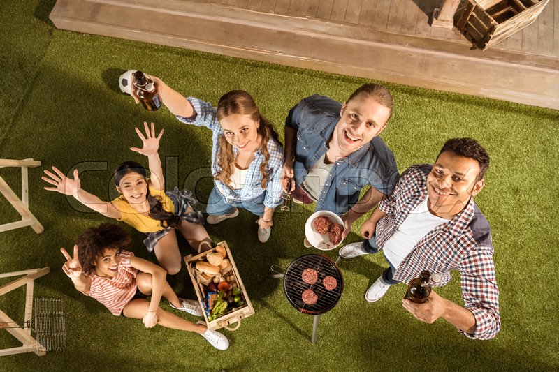 High angle view of happy young friends grilling burgers and drinking beer , stock photo