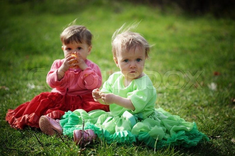 two baby girls sitting on the grass stock photo colourbox