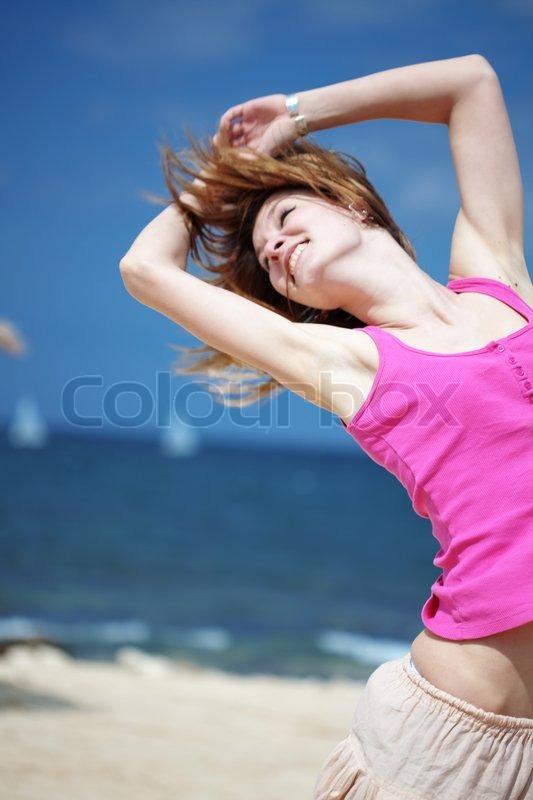 Teenage girl dancing hip-hop and jumping on beach, summer ...