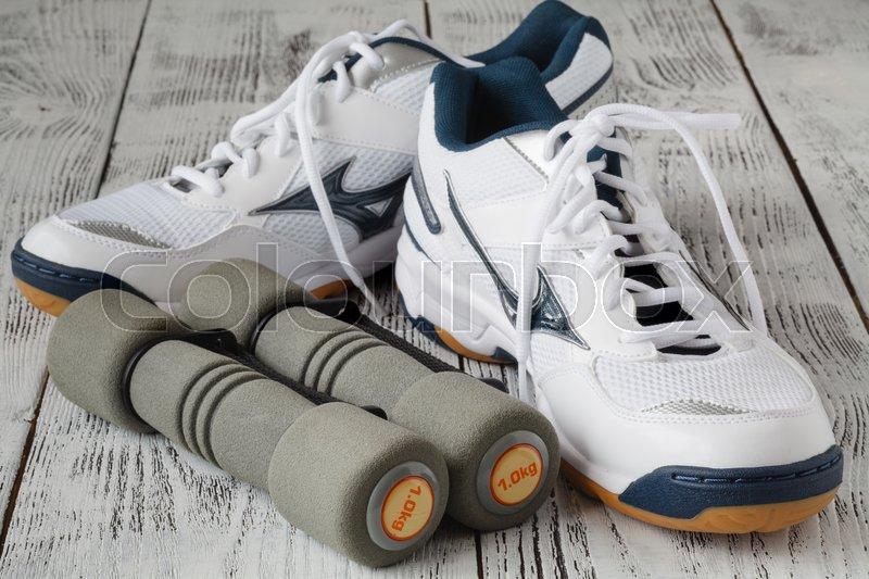 Sport shoes and dumbbells on the floor, top view. Sport background, stock photo