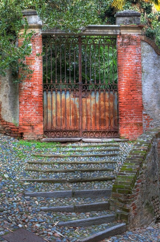 Vertical Oriented Image Of Old Rusty Gate In The Entry To