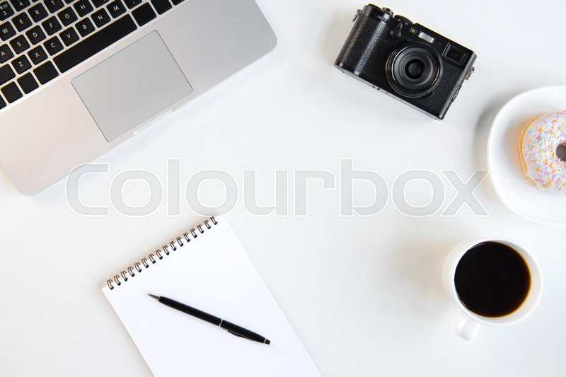 Top view of laptop, blank notebook with pen, cup of coffee and camera at workplace, stock photo