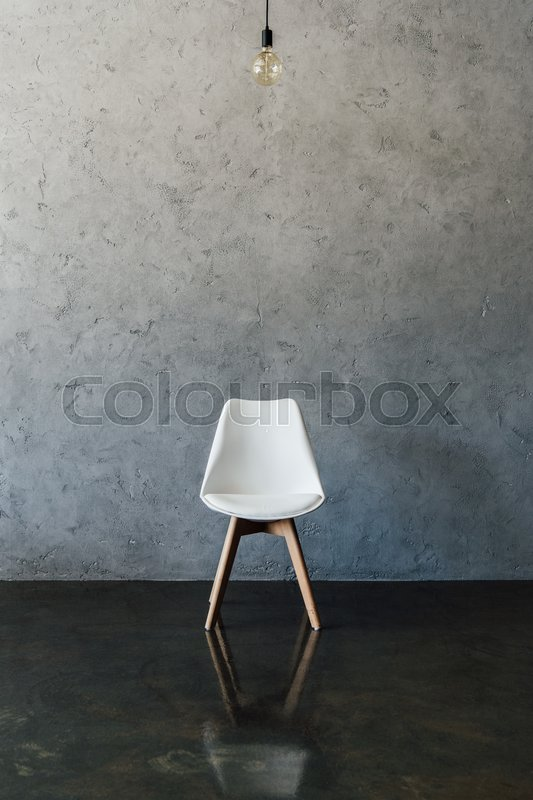 Electric bulb and modern white chair on the floor at empty room, stock photo