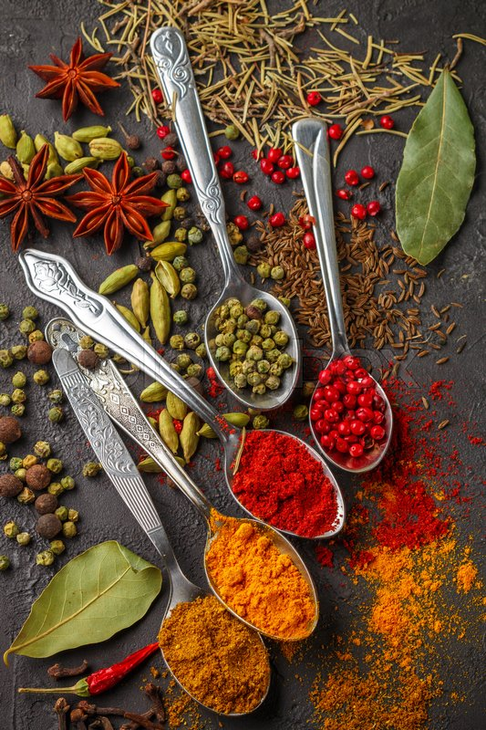 Variety of natural spices, seasonings and herbs in spoons on the stone table - paprika, curry, coriander, cardamom, turmeric, rosemary, salt, pepper, cumin, chili, cinnamon, cloves, star anise, salt, stock photo