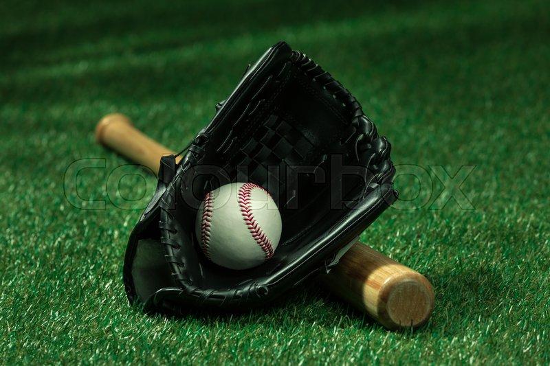 Closeup view of baseball bat, glove and ball lying on green field , stock photo