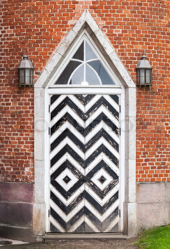Wooden door in red brick wall, Gothic Revival architecture style. Background texture, stock photo