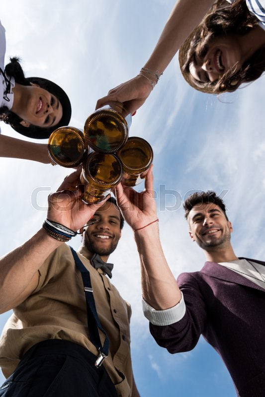 Low angle view of happy young friends clinking beer bottles outdoors , stock photo