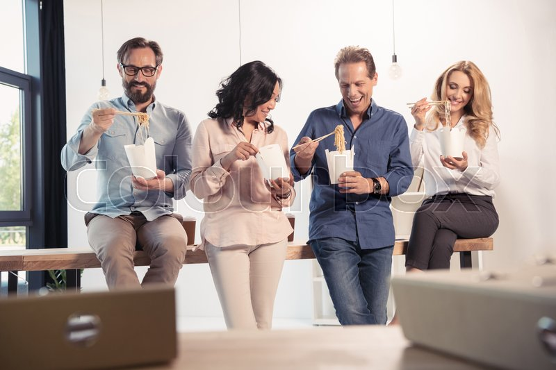 Smiling middle aged businessmen and businesswomen eating asian food in office, stock photo