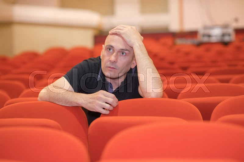 An artistic director reviewing actors in a theater, stock photo