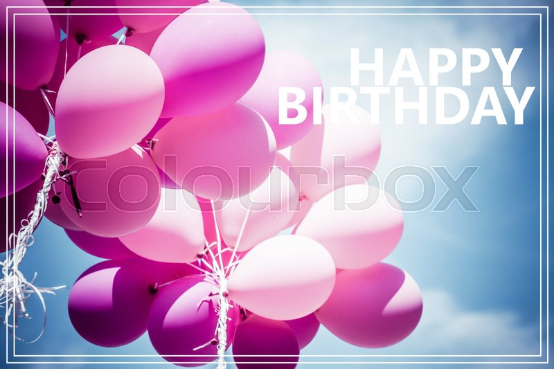 Word Happy Birthday over pink balloons and blue sky background, stock photo