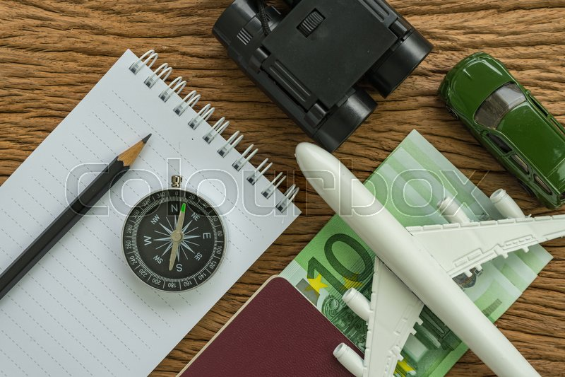 Travel planning concept with airplane, passport, compass, binoculars, pencil, paper note and Euro banknotes on wood table, stock photo