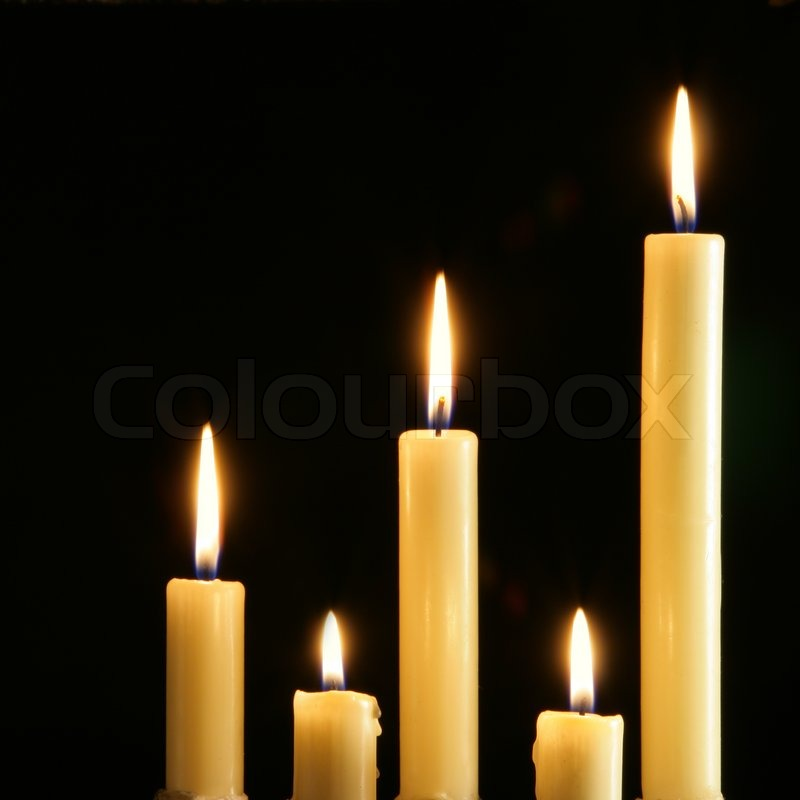 Five Burning Candles Over A Black Background Stock Photo