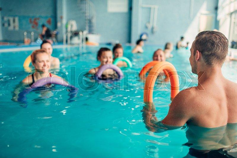 aqua aerobics exercises women class with male trainer indoor
