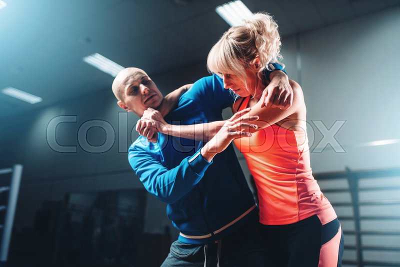 Woman fights with man, self defense technique, self-defense workout with personal trainer in gym, martial art, stock photo