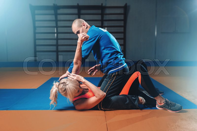 Woman fights with man, self-defense technique, self defense workout in gym, martial art, stock photo