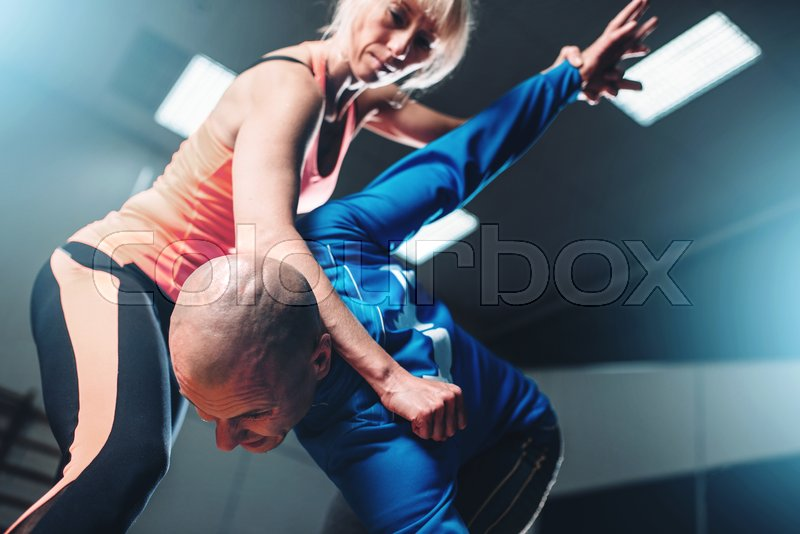 Male and female fighters, self-defense technique, self defense workout with personal instructor in gym, martial art, stock photo