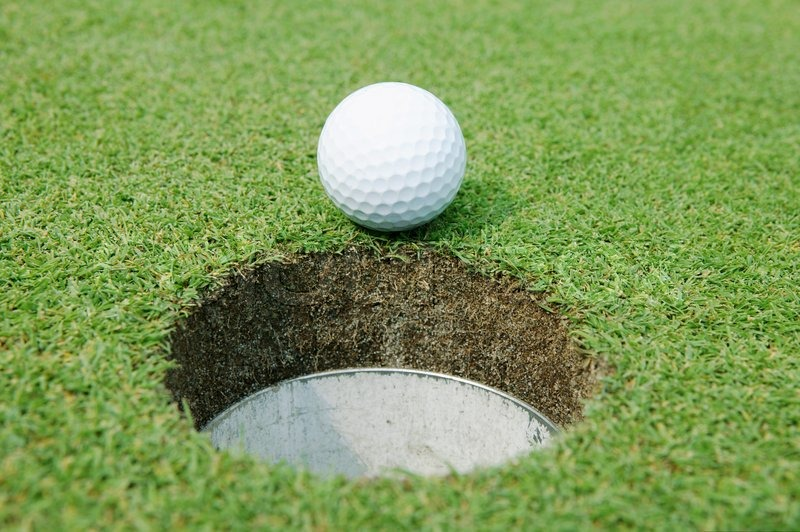 Close-up of a golf ball at the edge of the hole | Stock Photo ...