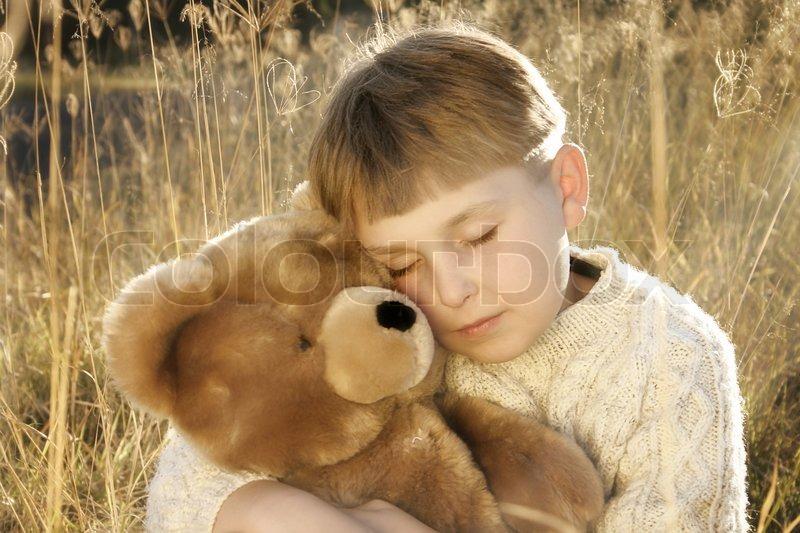 Boy In Tall Grasses Hugs A Teddy Bear Young Boy Cuddles