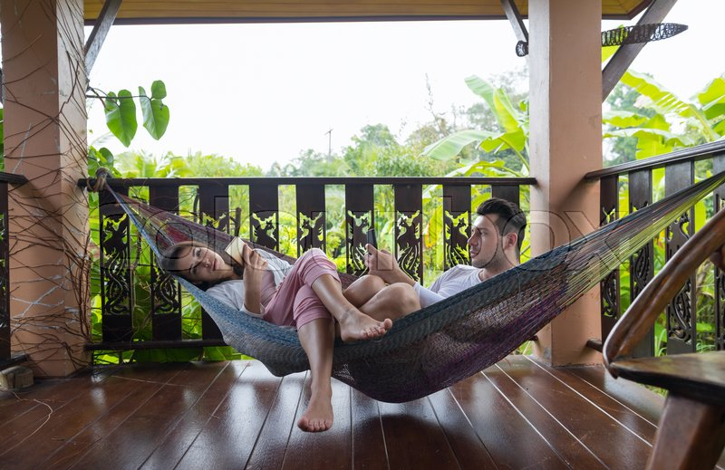 Young Couple Lying In Hammock On Terrace Tropical Hotel, Man And Woman Using Cell Smart Phone Chatting Tropic Holiday Vacation Green Forest, stock photo
