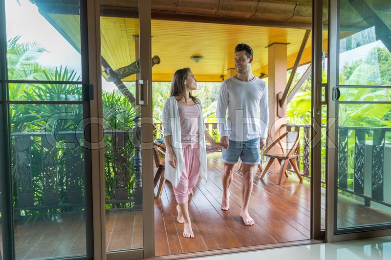 Young Couple On Terrace Tropical Hotel, Man And Woman Tropic Holiday Vacation Green Forest, stock photo
