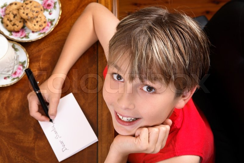 A child sitting at a desk writing a letter for Santa or Christmas card, stock photo