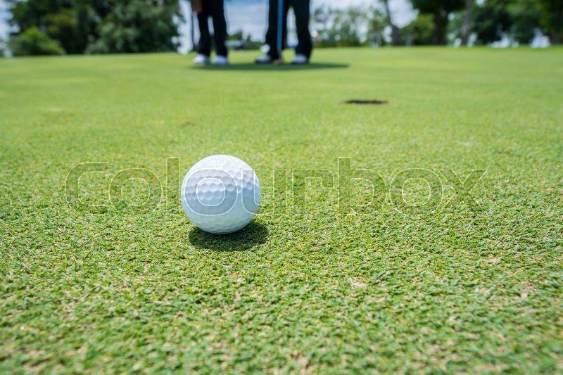 Golf ball on putting green, stock photo
