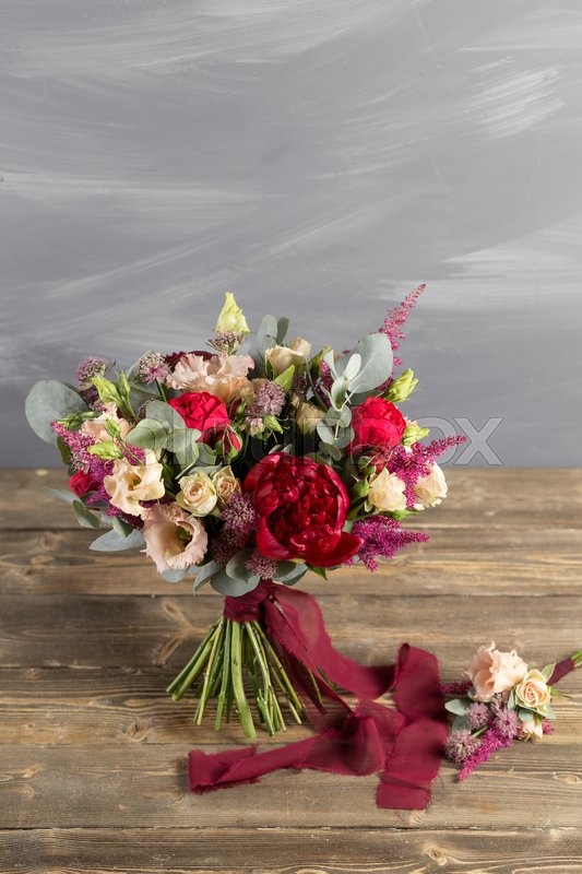 Bridal bouquet and boutonniere. Red and peach color flowers. stand ...