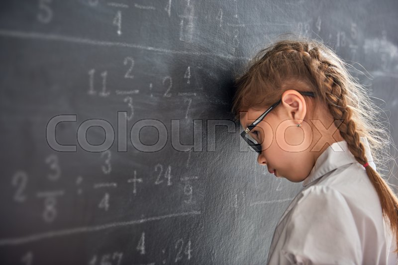 Tough day at school! Sad child near the blackboard indoors. Kid is learning in class. Complex math, arithmetic and examples. Numbers written with chalk on board, stock photo