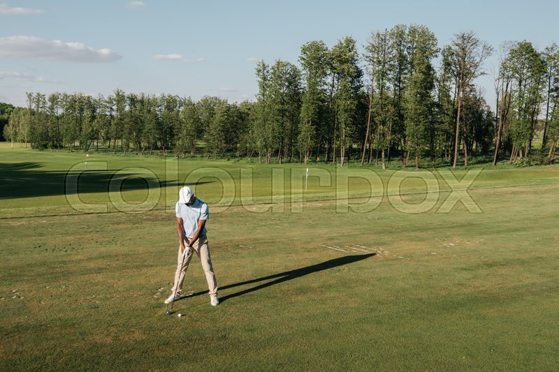 Full length view of man in cap holding golf club and hitting ball on green lawn , stock photo