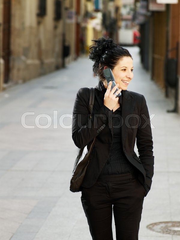 Young woman walking in street on phone, stock photo
