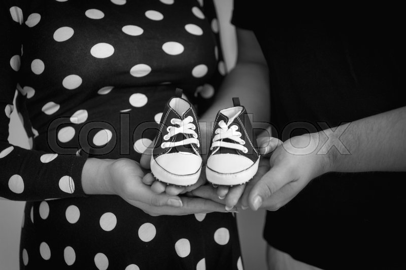 Closeup black and white photo of expectant parents holding baby boots on hands, stock photo