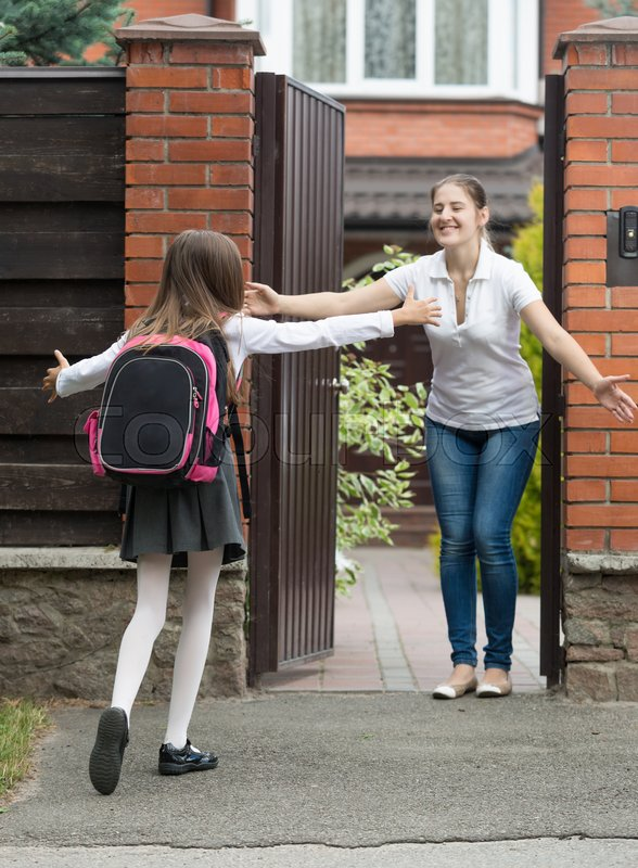 Cheerful young mother meeting her daughter after school in front of house, stock photo