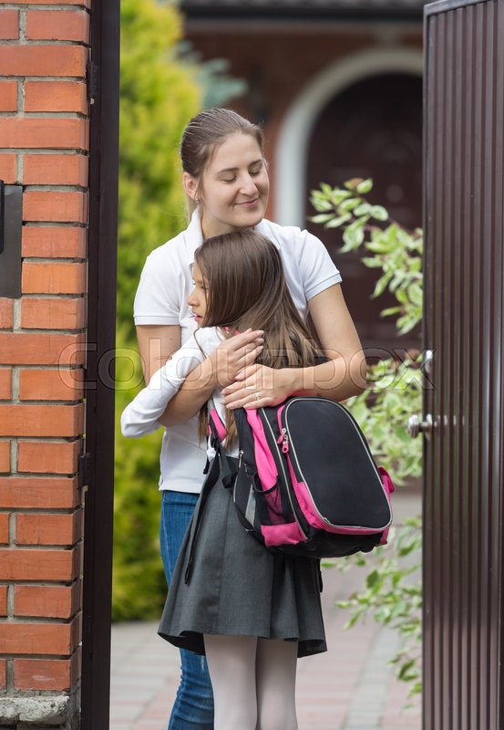 Happy young mother meeting her daughter after in school in front of house, stock photo