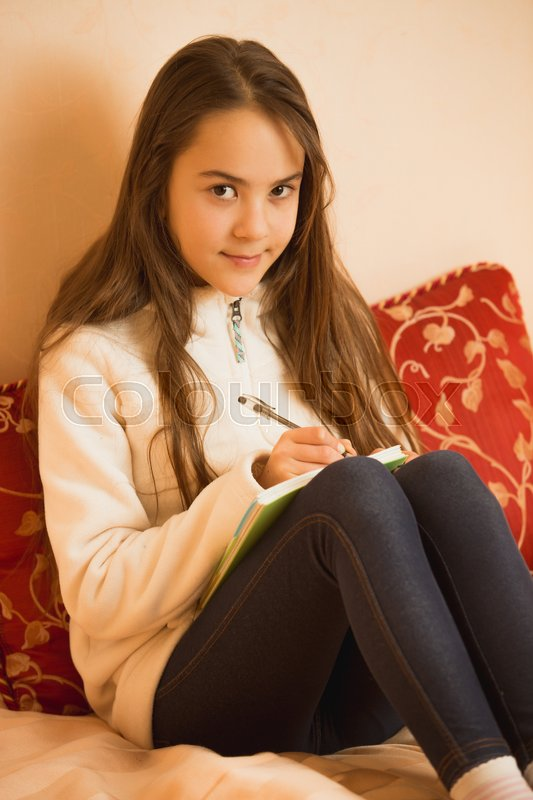 Brunette Teen Girl Writing In Diary At Bedroom