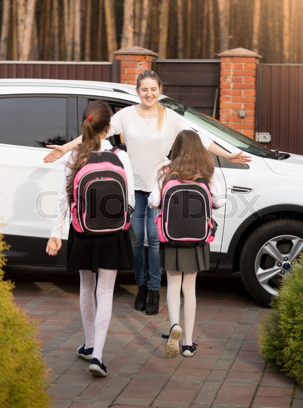 Happy young mother meeting her two daughters after school at car, stock photo