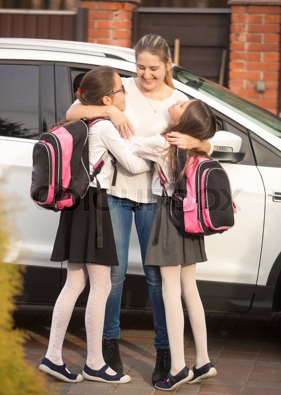 Happy mother meeting daughters near the car after school, stock photo