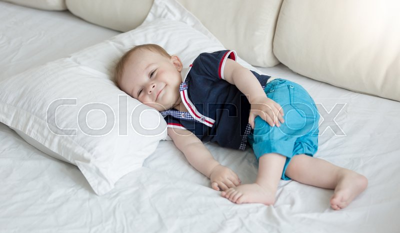 1 year old baby lying on big pillow on bed, stock photo