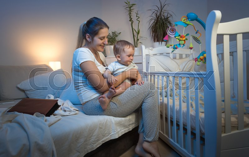 Beautiful young mother taking baby out of crib at night, stock photo