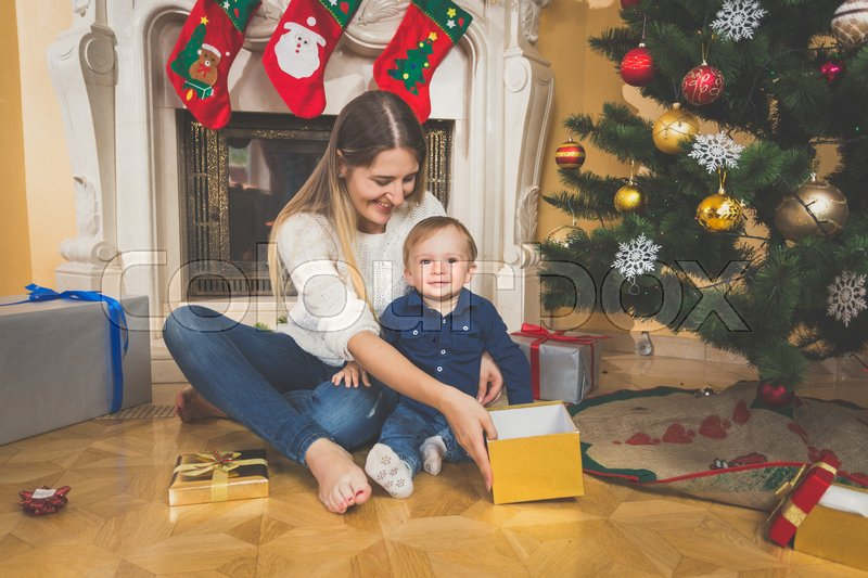 Smiling mother and baby on floor looking at Christmas gifts, stock photo