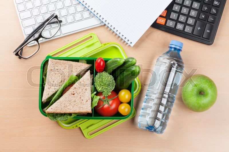 Office desk with supplies and lunch box with vegetables and sandwich. Top view, stock photo