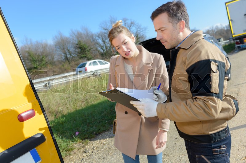 Woman signing insurance paperwork after a car breakdown, stock photo