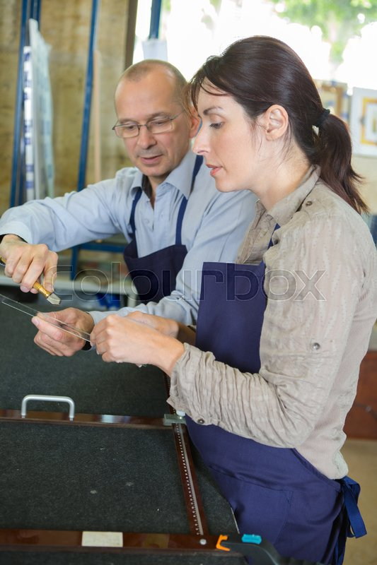 Senior shoemaker training apprentice to work with leather, stock photo