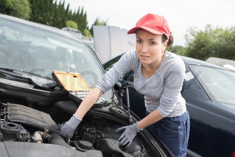Beautiful mechanic woman working on a car, stock photo