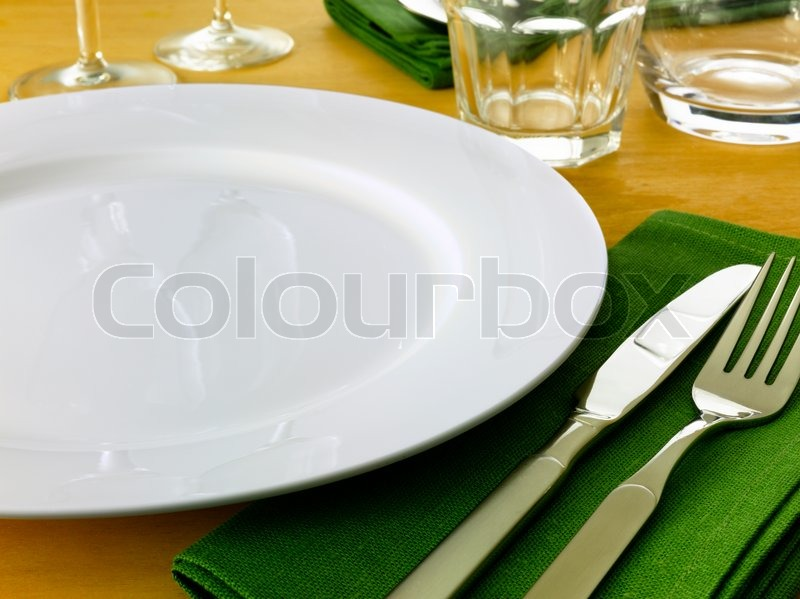 Table setting complete with plate knife and fork glasses and napkins ...