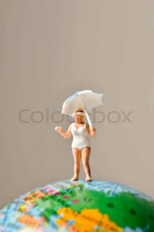 Stock image of 'a miniature old woman wearing swimsuit and holding an umbrella above her head on the top of the terrestrial globe'