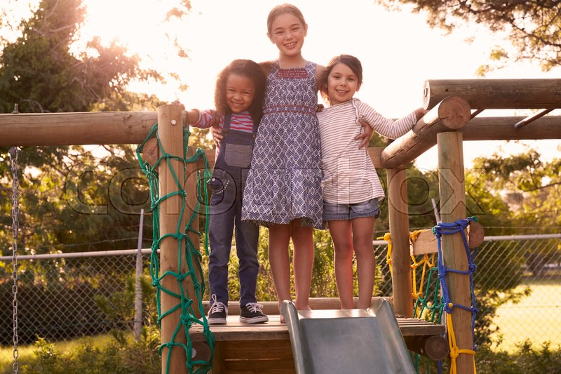 Three Girls Playing Outdoors At Home On Garden Slide, stock photo