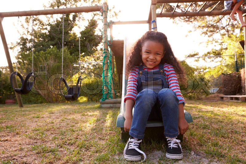 Portrait Of Girl Playing Outdoors At Home On Garden Slide, stock photo