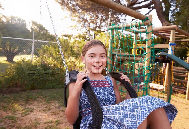 Girl Playing Outdoors At Home On Garden Swing, stock photo